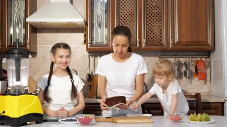 kalıp : Young brunette mother is baking birthday cake with her two little daughters in the kitchen, she is pulling the cake sponge out of the cake mold. Family cooking.