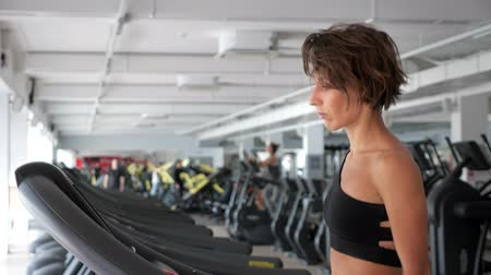 treadmill : Good looking and sporty woman is training on treadmill in gym. Mature woman is walking in quick step, side view. She is wearing in sportswear black top. Stock Footage