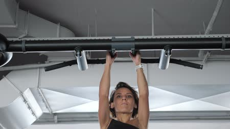 magro : Portrait of slim sporty woman is doing pull-ups on horizontal bar with a narrow grip in gym. Mature woman in sportswear, front view. Vídeos