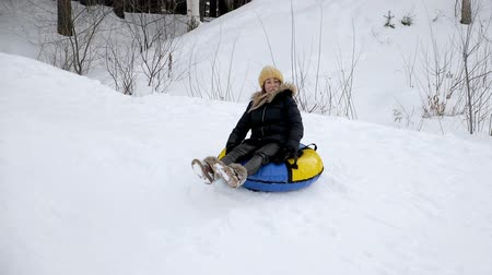 そり : Happy young woman is sliding from snow hill at tubing bouncing on bumps in slow motion. Winter outdoor activity.