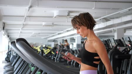 temp : Mature sporty woman is training on treadmill in gym and looking in mobile phone. She is walking in slowly temp warming up, side view. Fitness and sport concept. Stock Footage