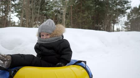 trubky : Happy kid boy in tubing is smiling and looking at camera. Young parents are running and sliding their son in tubing in winter park.