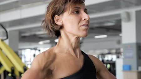 alívio : Portrait of sportive woman with relief body is lifting barbell making exercises for shoulders. Sports workout in the gym. Sport and fitness concept.