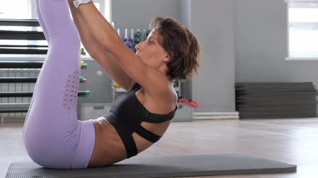 dres : Mature woman is doing crunches with free weight green disc on mat. She is pumping the abdominals in gym, side view. Sport and fitness concept.