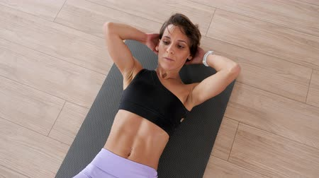 teszi : Athletic woman in sportswear is pumping the abdominals. She is doing abs exercise on mat in gym. Sport and fitness concept.