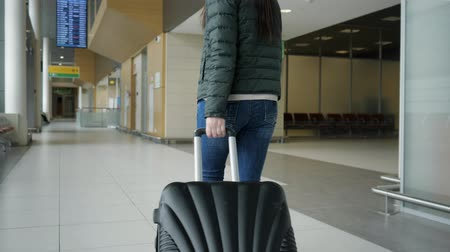 chegar : Traveler woman brunette is walking in modern airport terminal carrying suitcase, back view. Passenger is going to her flight in city airport. Vídeos