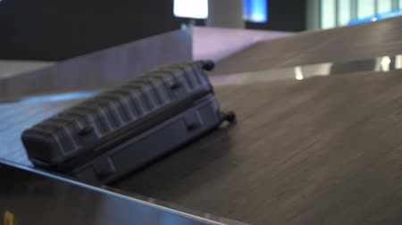 concourse : Big grey suitcase is moving on luggage conveyor belt in the airport terminal, closeup view.