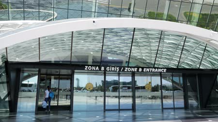 Baku, Azerbaijan, 20-05-2019: View at the entrance of Heydar Aliyev airport with woman entering the door. New modern airport terminal. Editorial video.