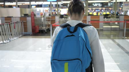 registrace : Young woman traveller is going to the registration desk in airport terminal. She is rolling suitcase and carrying backpack, back view. Dostupné videozáznamy
