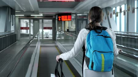chegar : Young woman traveller on escalator with backpack and suitcase in airport terminal. She is going to to the airport exit, back view.