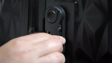 сочетание : Woman enters the code to open suitcase combination lock on the suitcase and presses the button, hands closeup.
