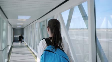 telescopic : Happy young woman with backpack is going on telescopic gangway to the airplane. She turns around, looks at the camera and smiles.