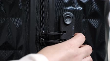 şifreleme : Woman enters the code to open suitcase combination lock on the suitcase and presses the button, hands closeup.