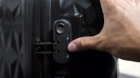 kombináció : Man is testing lock. He enters the code to open suitcase combination lock on the suitcase and presses the button, hands closeup. Stock mozgókép
