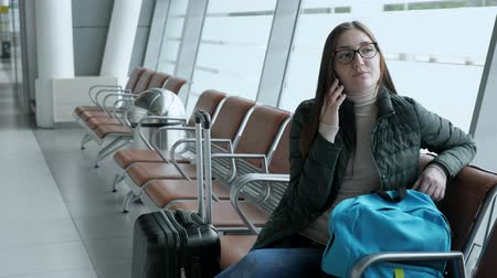 чемодан : Happy young woman in glasses is talking on smartphone looking forward to the rest. She is waiting her flight in airport sitting in hall with luggage. Стоковые видеозаписи