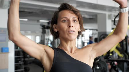 fisiculturismo : Athletic mature woman is making set of reps exercise with barbell lifting it over the head in gym. Sports workout in the gym.