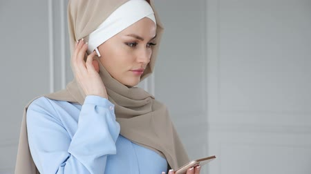 earpiece : Portrait of young muslim woman wearing hijab and traditional dress is listening music in mobile phone with close eyes using wireless earpiece and dancing. Stock Footage