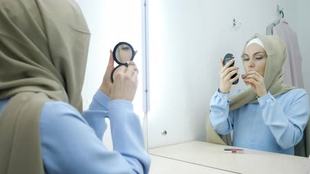 kompakt : Muslim young attractive woman in beige hijab and traditional blue dress making make-up and standing in front of the mirror. Stok Video