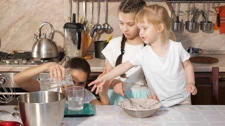 isteyen : Family cooking, mom pours some water into measuring cup, younger daughter wants to help her and holding out her hand. Woman explains recipe for her little girls. Stok Video