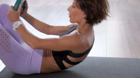 chroupat : Mature woman is doing crunches with free weight green disc on mat. She is pumping the abdominals in gym, side view. Sport and fitness concept.