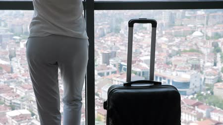 see off : Unrecognizable woman with suitcase in hotel room with panoramic city view, back view.
