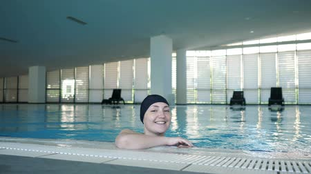 Деятельность выходные : Young woman in cap in swimming pool. She is looking at camera and smiling, front view. Sport and activity lifestyle.