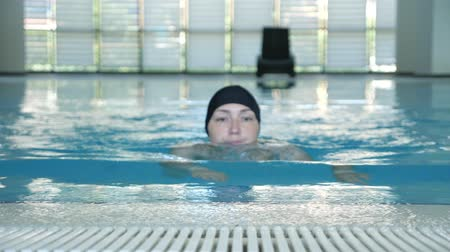 see off : Young woman in cap is swimming to the side of the pool. She is looking at camera and smiling, front view. Sport and activity lifestyle.