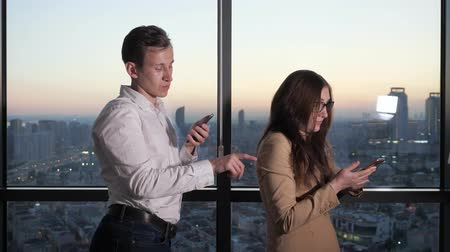 совращение : Man touches colleague woman for booty. They are near the panoramic window browsing smartphones during break. Sexual harassment in the office.