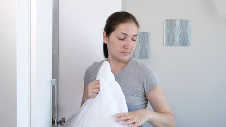 almofadas : Brunette young woman is going to sleep. She is taking out pillow and pillowcase from wardrobe, side view.