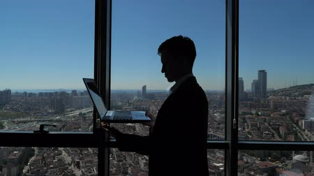 hayran olmak : Silhouette of businessman is working on his laptop in office. He is standing near the panoramic window with city view. Business concept.