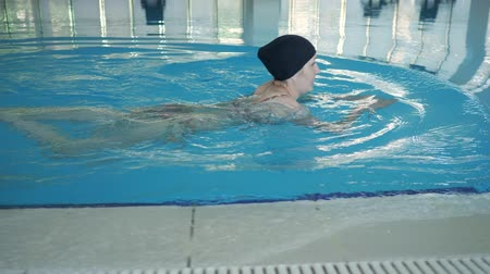 развлекательный : Young woman in swimming cap is floating freestyle on water surface in pool, side view. Стоковые видеозаписи