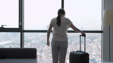 ubytování : Young brunette woman traveler with suitcase is entering in hotel room with panoramic city view. She is standing near the window and looking at city.