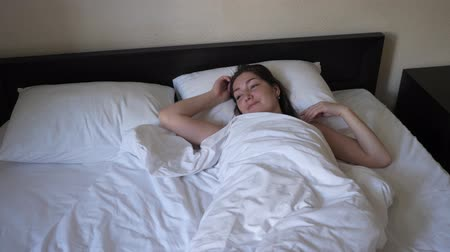 wakes : Brunette young woman is waking up in bed with white linen. She is remaining in her bed napping in morning in vacation. Comfortable sleep and rest.