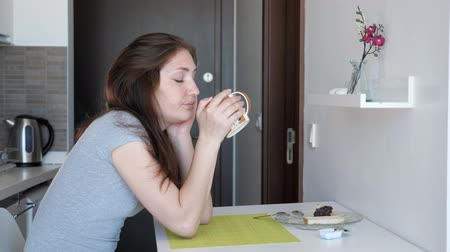 uykuda : Sleepy woman traveler is having a cup of tea sitting at small kitchen, side view. She is yawning and trying awake in renting apartment on vacation. Stok Video