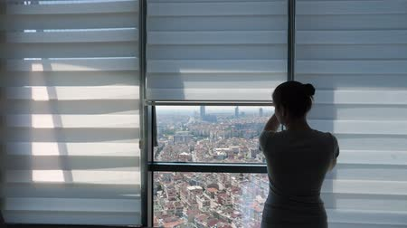 puxar : Woman is opening blinds in the morning in her modern apartment. She is looking at window with panoramic city view and stretching her arms. Vídeos
