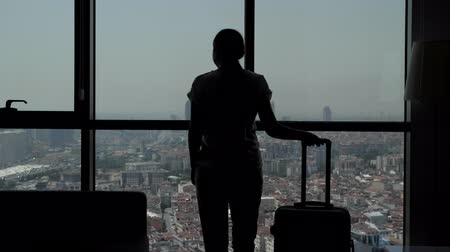 see off : silhouette of young girl traveler with suitcase is entering in hotel room with panoramic city view. She is standing near the window and dancing. Stock Footage
