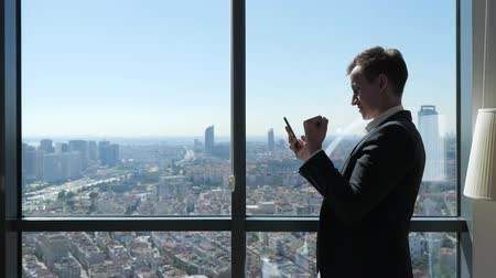 получать : Successful businessman is happy about getting great news on smartphone near window with panoramic city view. He is laughing and dancing celebrating victory in office. Winner concept.