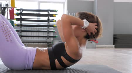 chroupat : Athletic woman in sportswear is pumping the abdominals. She is doing abs exercise on mat in gym, side view. Sport and fitness concept.
