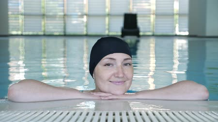 freckles : Young woman in cap looking at camera and smiling in swimming pool, close-up