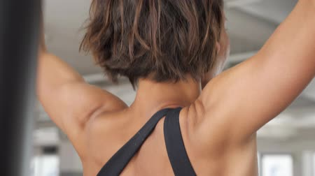 contra : Relief muscles on the womans back pulling up on the bar with wide grip in gym. Sport and bodybuilding concept.