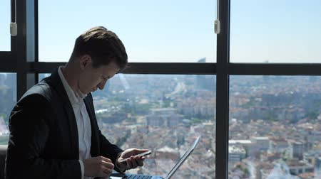 честолюбивый : Young businessman in suit is working with phone and laptop in office. He is sitting near the window with panoramic city view.