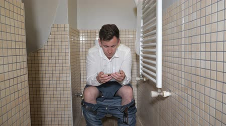 mocz : Man holds his smartphone to pass the time sitting on toilet bowl in lavatory. He plays on the mobile phone.