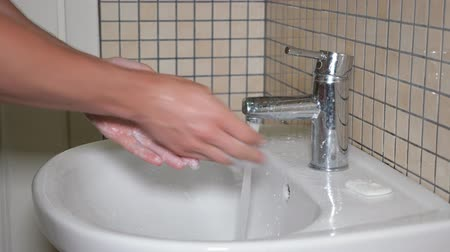 sanitize : Man is cleaning and washing his hands with antibacterial piece of soap in bathroom, closeup hands. Hygiene and body care concept.