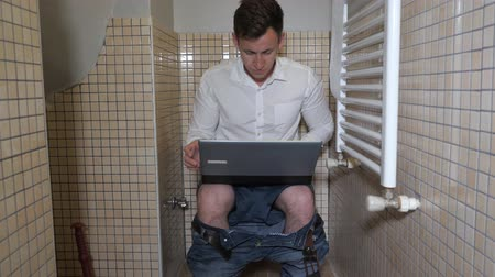 ищу : Inspired man workaholic is working in toilet on computer. He is typing something very quickly and thinking about it. Quiet place to work. Стоковые видеозаписи
