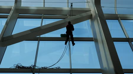 arruela : faceless worker man is washing windows with scraper on a highrise modern building hanging the rope.