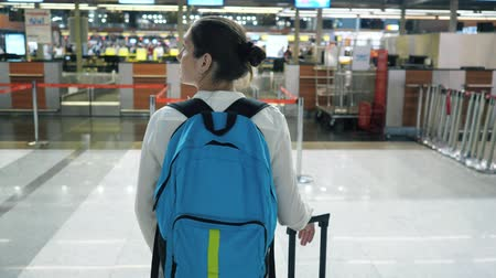 registration : Young woman traveller with backpack and suitcase in airport terminal building, close-up. She is standing and looking around, back view.