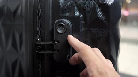 unlocking : man enters the code to open suitcase combination lock on the suitcase and presses the button, hands closeup.