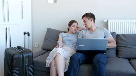 zęby : Young couple is booking transfer to the airport on laptop sitting on sofa at home. They are going on vacation with passports and suitcase. Choosing and booking tour and hotel.