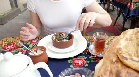 tekercselt : National traditional azerbaijan cuisine food in the restaurant. Woman is eating dolma with sour cream served in clay bowl, hands and table closeup. Girl in white t-shirt is eating with fork.