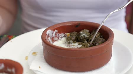 baku : National traditional cuisine food in the restaurant. Woman is eating dolma with sour cream served in clay bowl, dish closeup. Girl is eating with fork putting the sour cream using spoon.